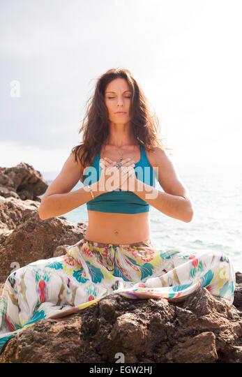 Woman meditating on rocks near ocean. - Stock-Bilder