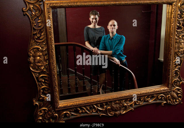 Young couple standing on stairs reflected in a large mirror - Stock Image