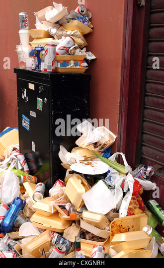Food waste and drinks cans littering the pavements - Stock Image