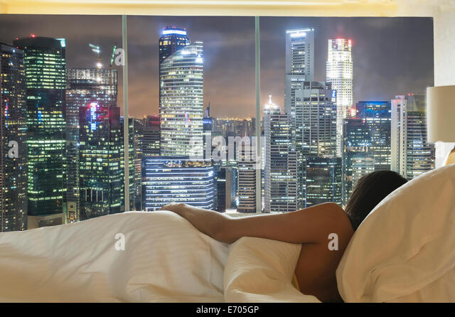 Young woman lying in bed looking at city skyline through window - Stock Image