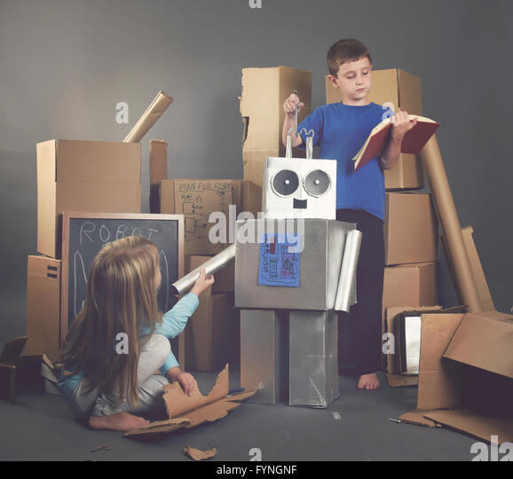 Two Children are building a metal robot from cardboard boxes with tools and books for an imagination, science, education - Stock Image