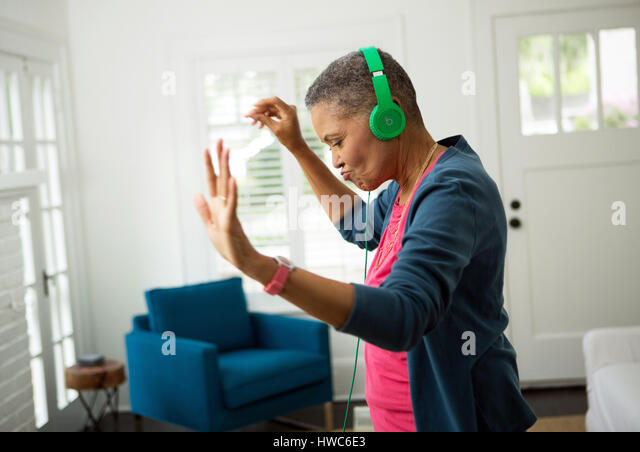 Senior woman listening to music on headphones - Stock Image