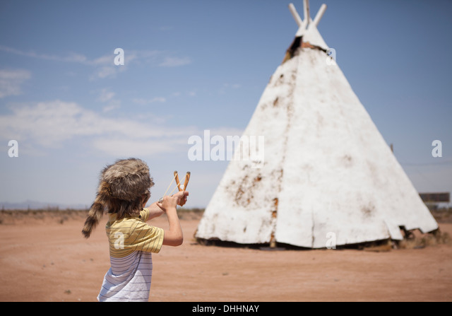Boy aiming slingshot at teepee, Indian Reservation, USA - Stock Image