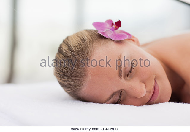 Woman laying with orchid in hair - Stock Image