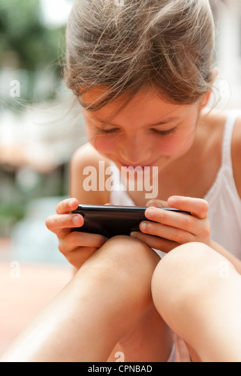 Girl playing with smartphone - Stock-Bilder