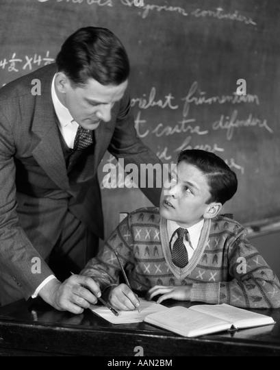 1920s CLASSROOM MALE TEACHER HELPING BOY AT DESK - BLACKBOARD IN BACKGROUND - Stock Image