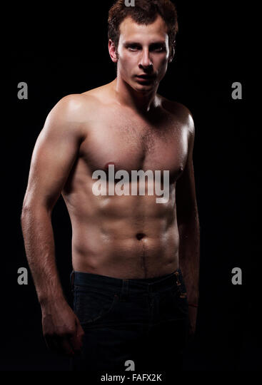 The beautiful and strong young  guy.  Photoshoot in a studio, dark background. - Stock Image