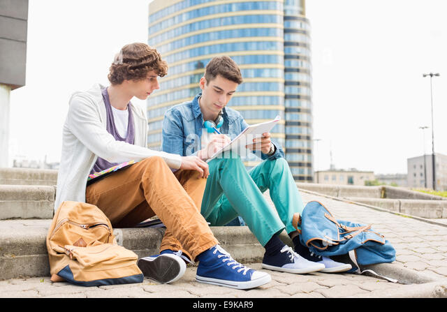Full length of young male college students studying on steps against building - Stock Image