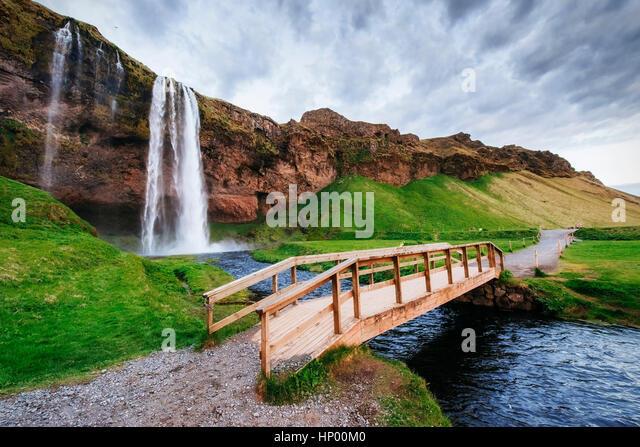 Seljalandfoss waterfall at sunset. Bridge over the river. Fantas - Stock Image