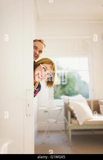 Portrait playful mature couple peering from behind door - Stock Image