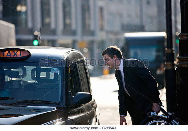 A businessman with his folded bicycle, talking to a taxi driver - Stock Image