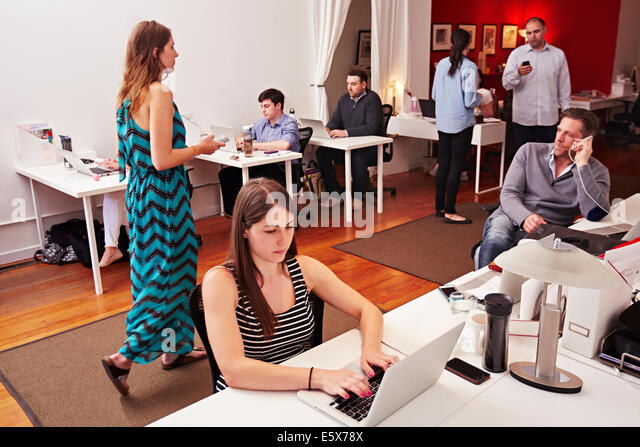 People at work in busy modern office space - Stock Image