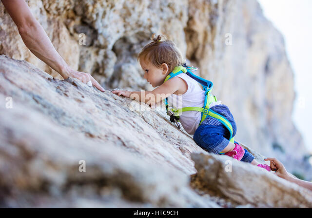 Little girl in safety harness climbing up cliff, mom and dad safeguarding her from above and beneath - Stock Image
