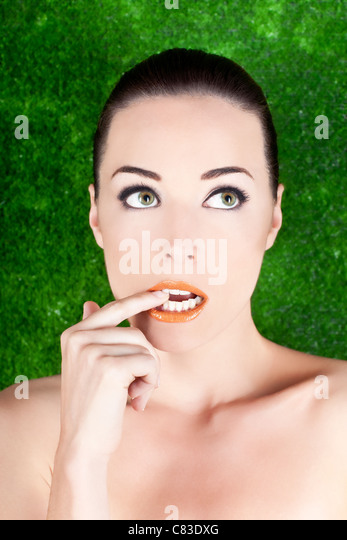 Closeup portrait of a beautiful nervous woman biting her finger while looking up isolated on green - Stock Image