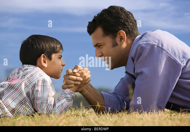 Hand wrestling between son and father - Stock Image