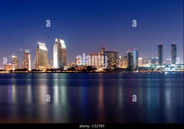 The San Diego skyline is illuminated at dusk as seen from Coronado Island, CA. - Stock-Bilder