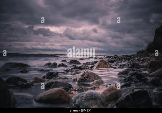 Large rocks on stormy, overcast nighttime beach, Bisserup, Denmark - Stock-Bilder
