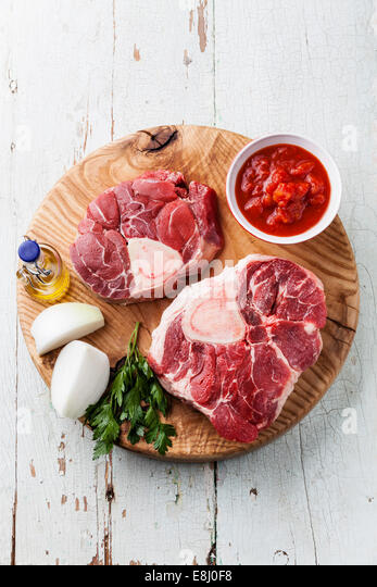 Raw fresh beef shins for making Osso Buco on wooden cutting board on blue wooden background - Stock Image