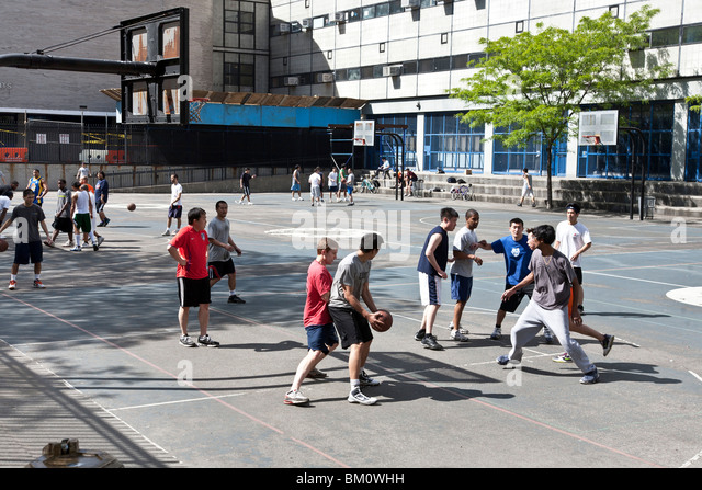 multiethnic street basketball game underway in spring sunshine on high school playground in 'Hells Kitchen' - Stock Image