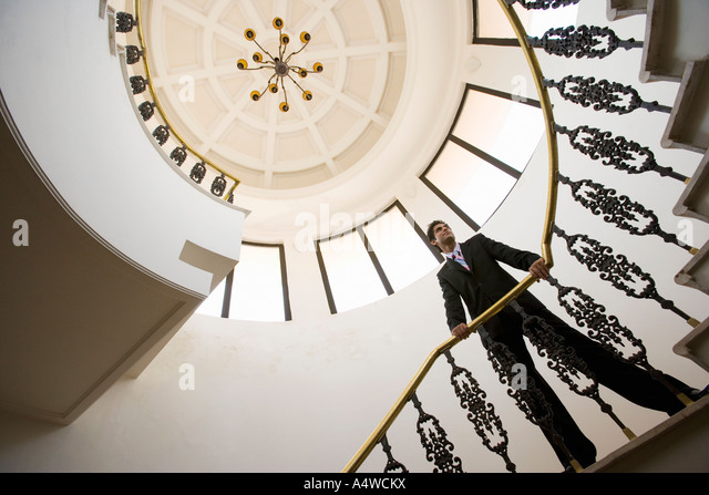 Businessman on spiral staircase - Stock-Bilder