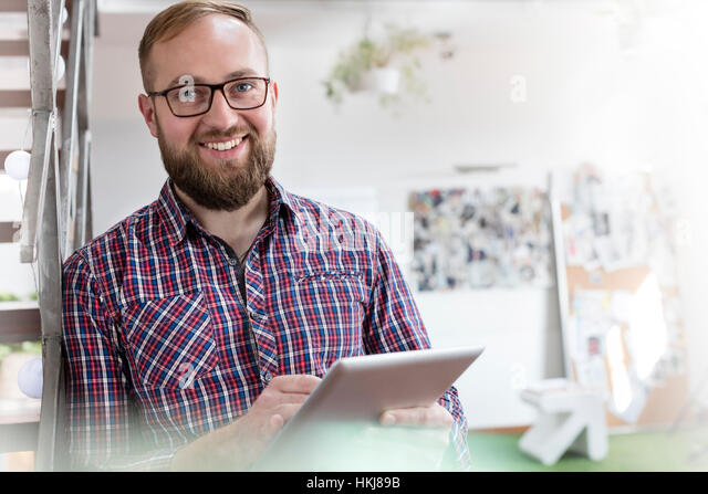 Portrait smiling male design professional using digital tablet in office - Stock Image