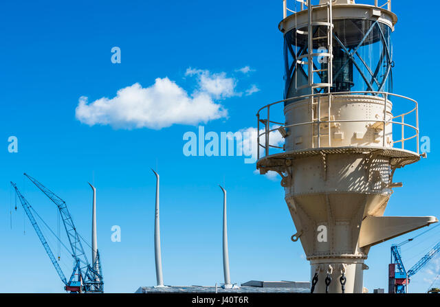 A historical signal light and the masts of a modern sailing ship with the cranes of a shipyard in the harbour, Kiel, - Stock Image
