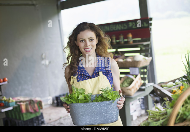 An organic farm stand. A woman sorting vegetables. - Stock Image