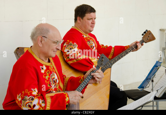 Ukraine, Yalta, Livadia Palace. Ukrainian folkloric show with traditional costumes. Men playing Russian three-stringed - Stock Image