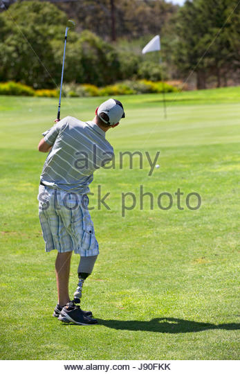 Rear View Of Male Golfer With Artificial Leg Approaching Green - Stock-Bilder