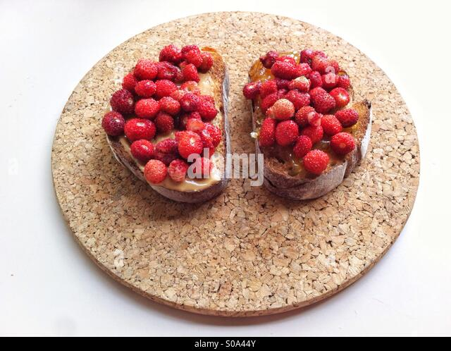 Peanut Butter and wild strawberries sandwich on gray bread served on cork board - Stock Image