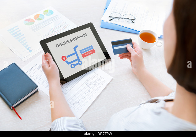 Caucasian businesswoman sitting at the desk in the office and using credit card and modern digital tablet for online - Stock Image