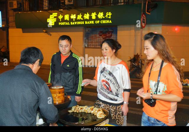 Shanghai China Huangpu District Sichuan Road street food vendor night Asian man woman Chinese Mandarin symbols hanzi - Stock Image