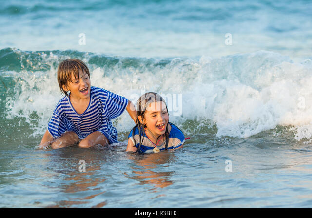 Two children playing in the sea - Stock Image