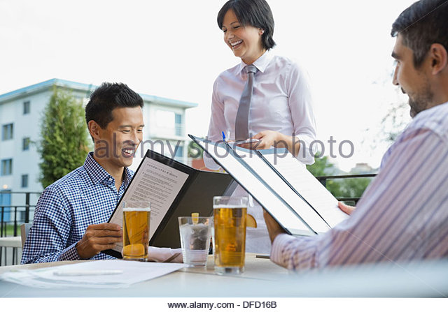 Cheerful waitress taking order from businessmen at outdoor cafe - Stock Image