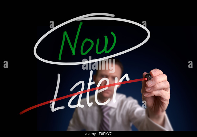 A businessman writing a, Choosing Now instead of Later, concept. - Stock Image