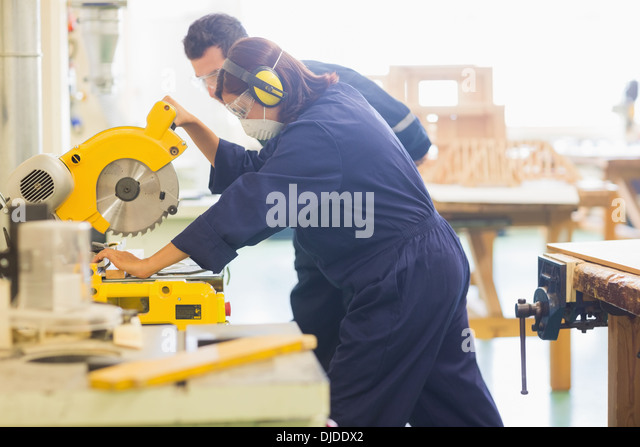Concentrating trainee sawing piece of wood - Stock-Bilder