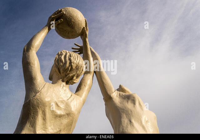 White stone statue of two women playing netball against a blue sky - Stock Image