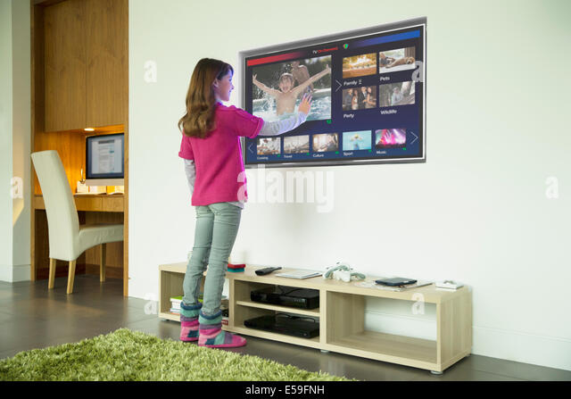 Girl using touch screen television in living room - Stock Image