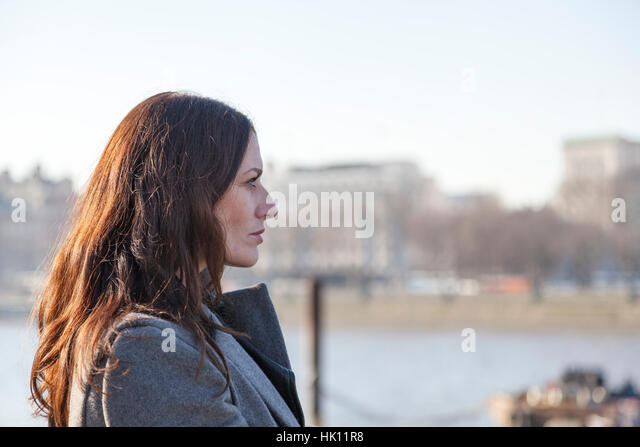 An attractive woman with long dark hair looks out onto a river - Stock Image