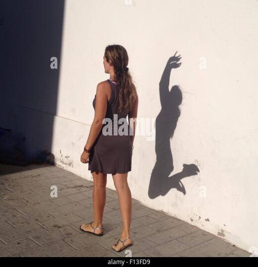 Woman walking past a wall with her shadow dancing - Stock-Bilder