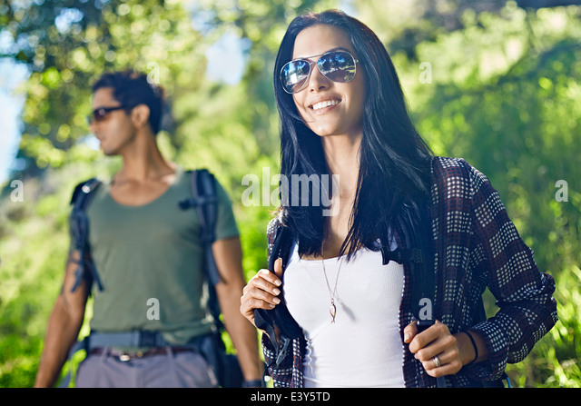 Couple walking with backpacks in forest - Stock Image
