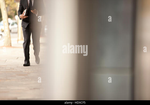 Business man checks phone while walking - Stock Image