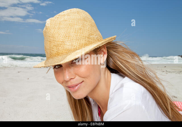 Portrait of smiling woman on beach in straw hat, Cape Town, South Africa - Stock Image