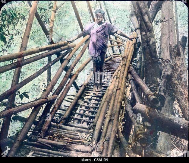Ein indisches Kind steht auf einer aus Bambus gefertigten Brücke über einer Dschungelschlucht. India, - Stock Image