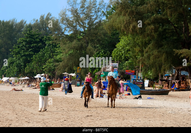 beach life at funky fish restaurant in Long beach tourists on horses Koh Lanta Thailand - Stock Image