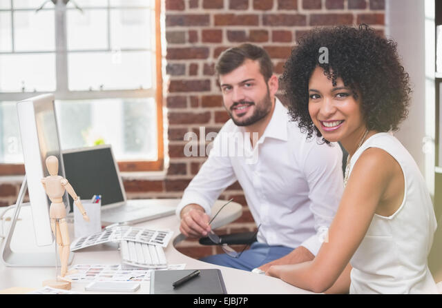 Smiling photo editors in office - Stock Image