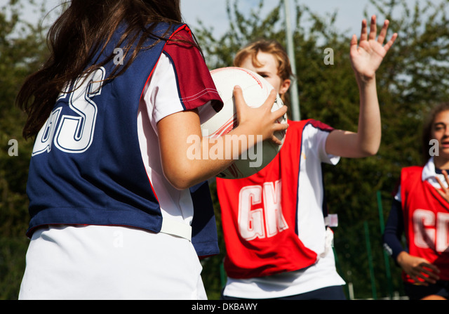 Teenage schoolgirl netball players defending - Stock Image