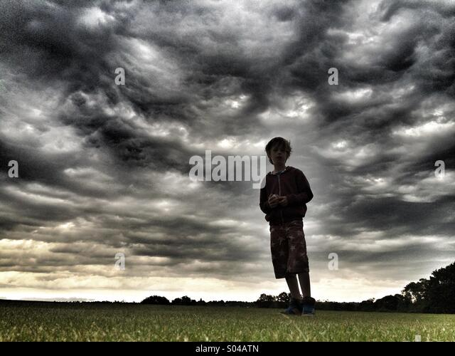 Silhouette of boy against stormy sky - Stock Image