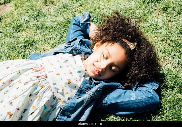 High angle view of girl lying on back on grass, hands behind head, eyes closed - Stock Image
