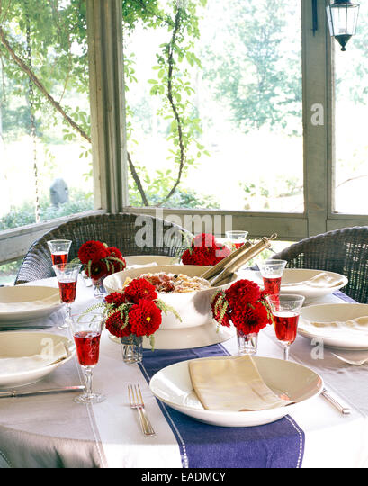 Summer meal on set table in screened in porch - Stock Image